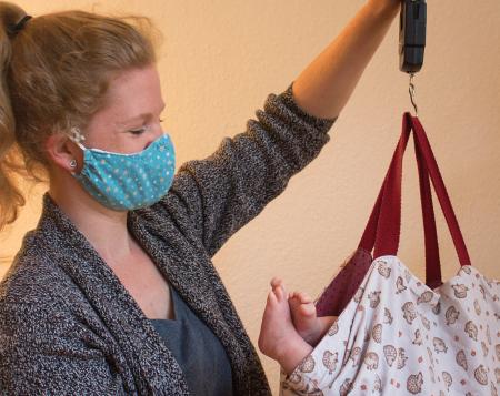 Ein Bild der Hebamme Rebecca Teetzen, wie sie mit Mundschutz ein Baby wiegt.